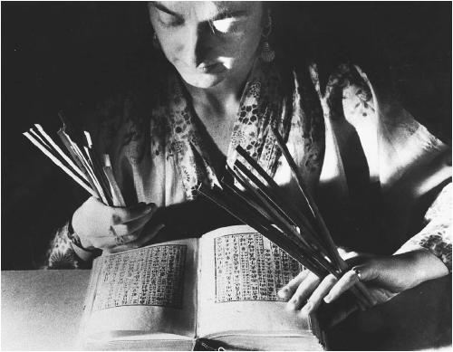 Woman consulting with the book I Ching and using fortune sticks. (FORTEAN PICTURE LIBRARY)