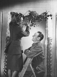 Man and woman  hanging mistletoe. (CORBIS CORPORATION)